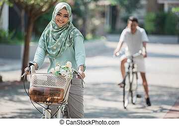 muslim woman riding a bicycle