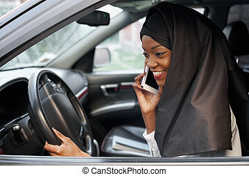 Muslim woman sitting in car talking by mobile phone.