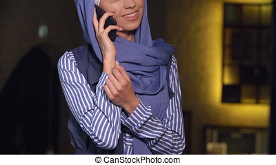 Muslim woman smiling talking on a cell phone