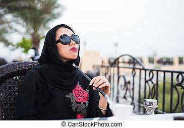 Muslim woman smoking shisha outdoors