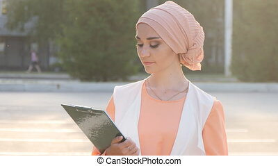 Muslim woman standing with document paper outdoor