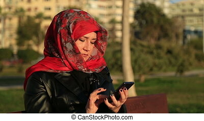 Muslim woman talking on the smart p