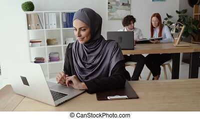 Muslim woman texting on a laptop during a little break from work. Happy smile, romantic mood and falling in love.