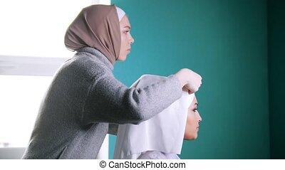 Muslim woman tying Islamic turban for attractive bride,...