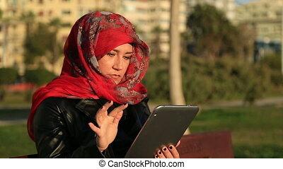 Muslim woman using digital tablet