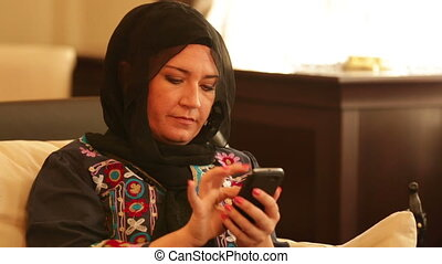 Muslim woman using smart phone
