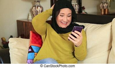 Muslim woman using smart phone - Smiling muslim woman using...