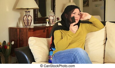 Muslim woman watching tv - Muslim woman sitting on a sofa...