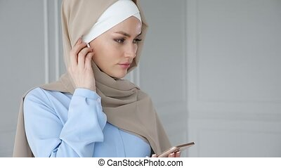 Muslim woman wearing hijab is listening music in smartphone...