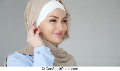 Muslim woman wearing hijab is putting wireless earphone in...