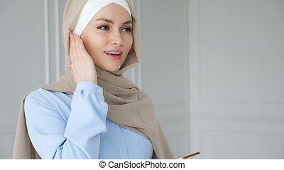 Muslim woman wearing hijab is speaking smartphone using...