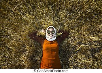 Muslim woman wearing hijab relaxing on savanna
