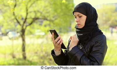 Muslim woman with a tablet in her hands outdoors.