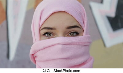 Muslim woman with her head covered with pink scarf . Full hd video