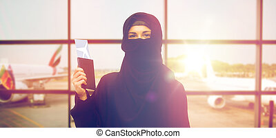 muslim woman with ticket and passport at airport - travel,...