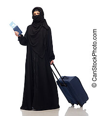 muslim woman with ticket, passport and travel bag