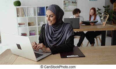 Muslim woman working on a laptop in the office with her Christian coworkers. Lifted mood and head full of creative ideas.
