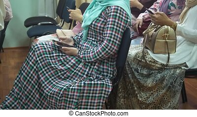 Muslim women in long dresses at the islamic conference uses...