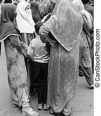Several women dressed in Muslim garb converse in an urban setting
