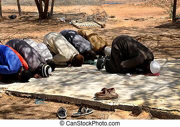 Muslims praying in congregation outside, islamic Prayer