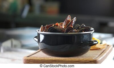 Mussels and fries, wooden board. Delicious restaurant meal.