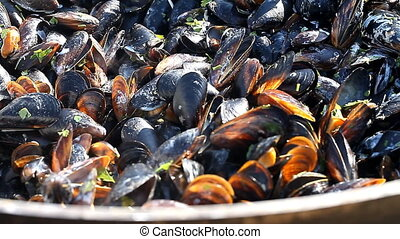 Mussels cooked in a large pan over a fire