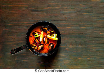 Mussels in red curry sauce on a wooden background.