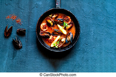 Mussels in red curry sauce on blue background.