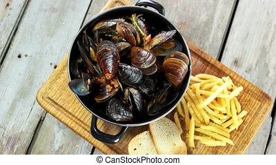 Mussels with toasts and fries. Restaurant meal top view.
