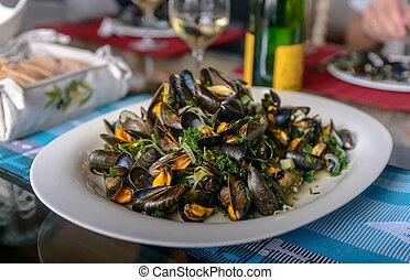 musslor, in, a, porslin, tallrik, på, a, bord, mot, den, bakgrund, av, a, flaska vin