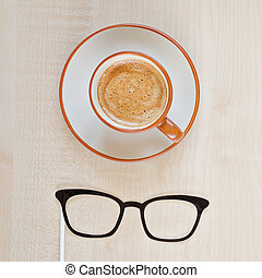 Mustache, glasses and cup of coffee on wooden background....