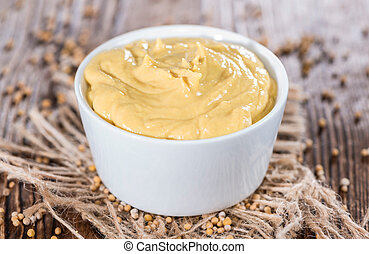 Mustard in a small bowl on vintage wooden backround