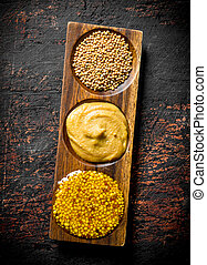 Mustard in a wooden stand.