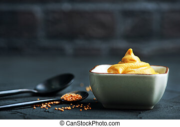 mustard in bowl and on a table