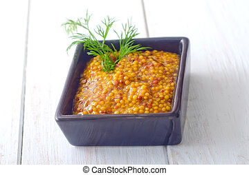 Mustard in the black bowl on table