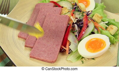 Mustard On Spam - Mustard being spread on to slices of spam...