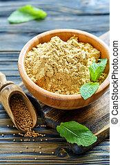 Mustard powder in a wooden bowl.