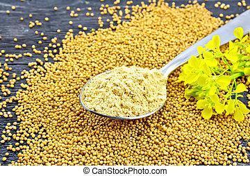 Mustard powder in spoon with flower on black board