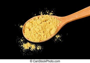 Mustard Powder in Wooden Spoon on Black Background