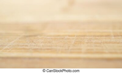 Mustard seeds being poured on light wooden cutting board,...