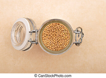 Mustard seeds in glass on brown background