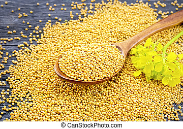 Mustard seeds in spoon with flower on board