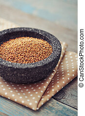 Mustard seeds in stone bowl on wooden background. Selective ...