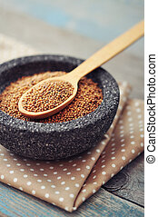 Mustard seeds in stone bowl on wooden background. Selective...