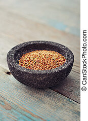 Mustard seeds in stone bowl on wooden background. Small ...