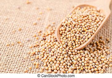 Mustard seeds in wooden scoope