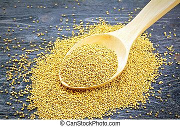 Mustard seeds in wooden spoon on black board
