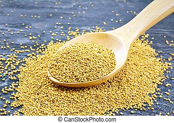 Mustard seeds in wooden spoon on board