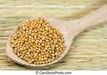 mustard seeds on a wooden spoon