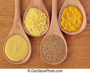Mustard selection of dijon, powder, seeds and english in wooden spoons over oak background.